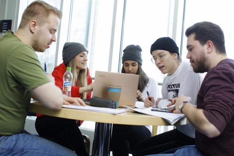 Fysiikan opiskelijat Eetu Räsänen (vas.), Henna Kokkonen, Philson Aden, Emmi Rajala ja Samuli Aalto arviovat uuden opetusmallin hyväksi, sillä se jakaa töitä tasaisesti koko viikolle.