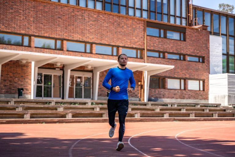 Mies juoksee Seminaarinmäen urheilukentällä.